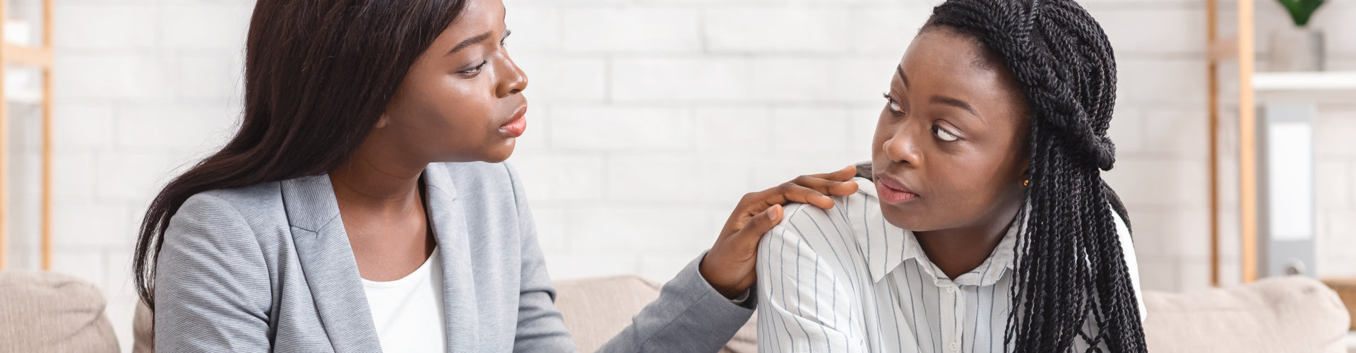 Psychotherapist comforting sad female patient during therapy session in office